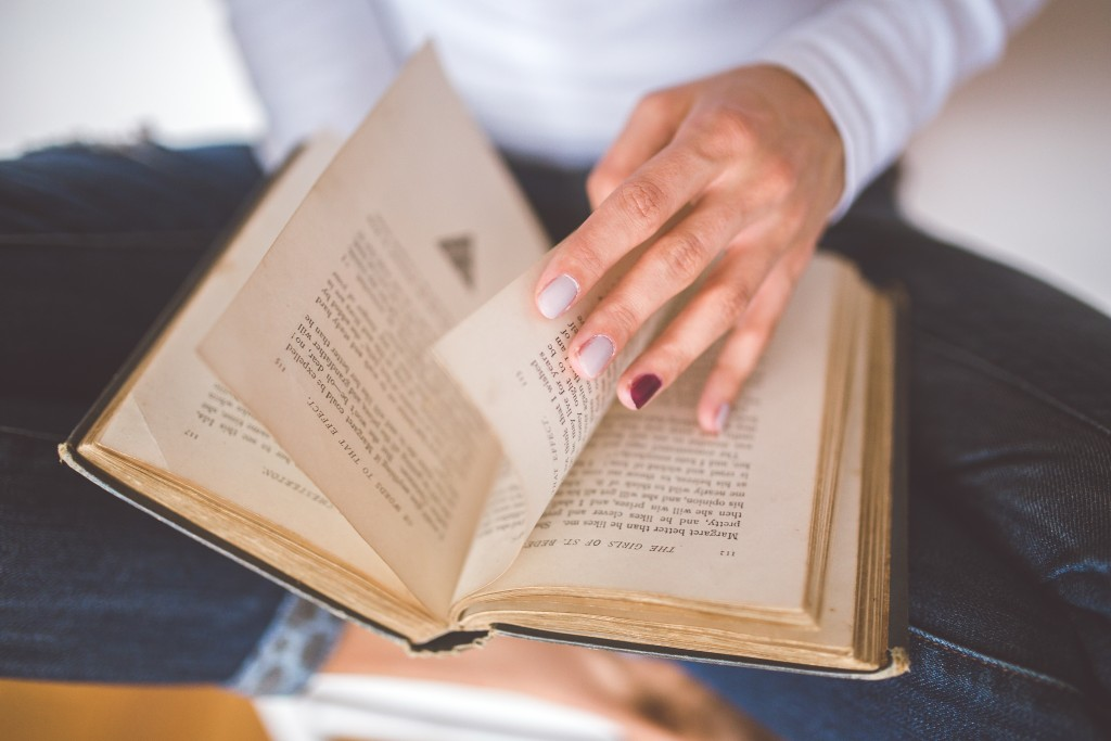 kaboompics.com_Girl thumbs through the old book